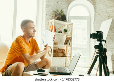 Young caucasian male blogger with professional camera recording video review of tablet at home. Blogging, videoblog, vlogging. Man making vlog or live stream about photo or technical novelty.