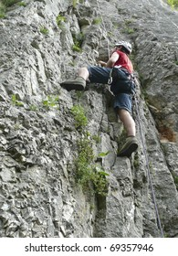 Young Caucasian male climbing on a lime rock wall using safety ropes.