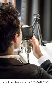 Young Caucasian Male with Dark Hair Speaks into a Microphone in a Podcast Studio