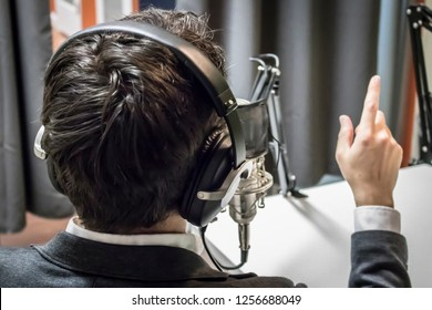 Young Caucasian Male with Dark Hair Speaks into a Microphone and Points his Index Finger in a Podcast Studio