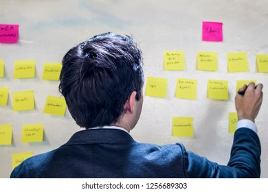 Young Caucasian Male with Dark Hair Reads Notes on Pink and Yellow Sticky Notes on a White Wall in a Corporate Office