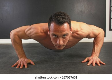 Young caucasian male doing push ups. Front view.