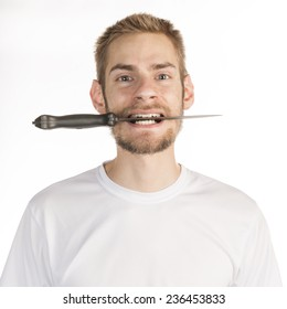 Young Caucasian male in his 20s with a knife in his mouth isolated on white