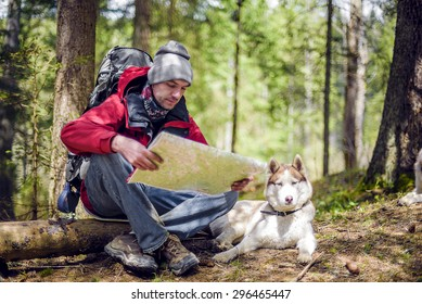 young caucasian male with a map and siberian husky dog in the forest, hiker looking at map outdoors