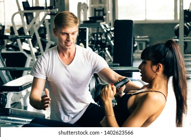 Young Caucasian male personal trainer in white shirt at a gym, helping and supporting female fitness client. She is doing situps. Sport fitness and muscles concept