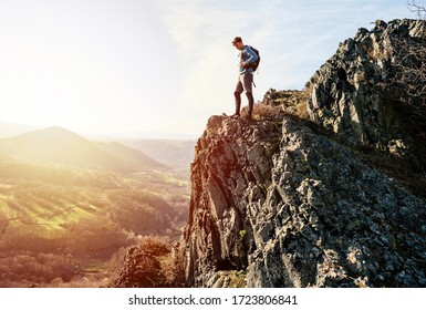 Young caucasian male traveler on high top of rock looking at valley enjoying wild environment landscape during sunset. Discovery, Travel, Adventure