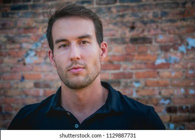Young caucasian man against a brick background with a concerned facial expression.