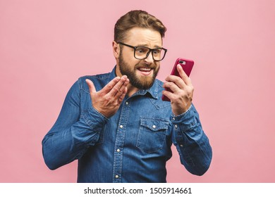 Young caucasian man angry, frustrated and furious with his phone, angry with customer service. Isolated over pink background.