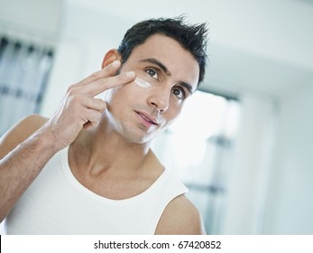 young caucasian man applying eye cream on face. Horizontal shape, front view, head and shoulders