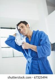 young caucasian man in blue bathrobe drying hair. Vertical shape, three quarter length, copy space