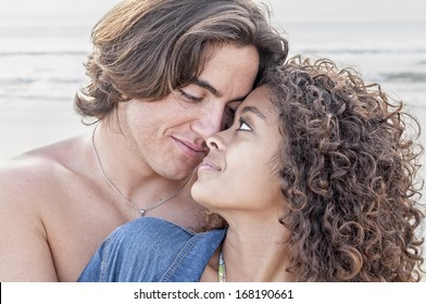 Young Caucasian man closely embraces young pretty Hispanic woman while gazing into each others eyes on beautiful beach