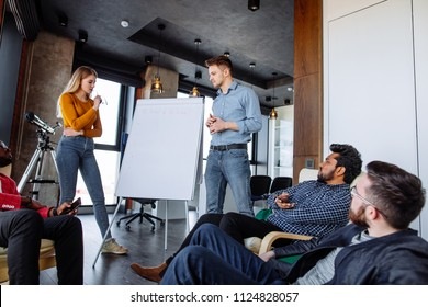 Young caucasian man coach holding flip chart, explaining studying materiel in stylish meeting room in office. Group of sales managers and reps discussing written on board during lesson.