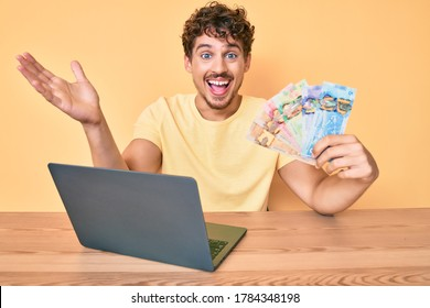 Young caucasian man with curly hair sitting on the table working with laptop and holding canadian dollars banknotes celebrating victory with happy smile and winner expression with raised hands
