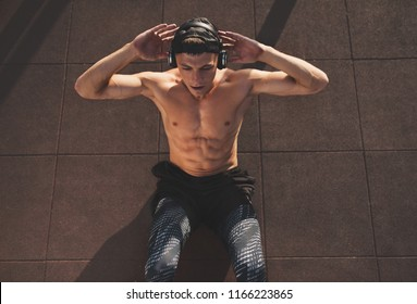 Young Caucasian man doing sit-ups and listening the music from his headphone. Top view of handsome shirtless man model exercising outdoors.