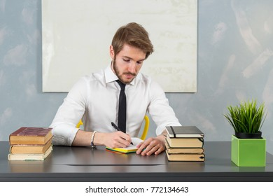 Young caucasian man dressed with a white shirt and a tie working at a desk office