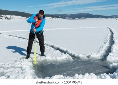 Young Caucasian man drilling the ice on a frozen lake with ice auger drill. Selective focus