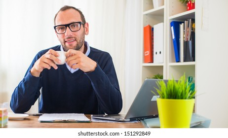 A young caucasian man drinking coffee in his office.