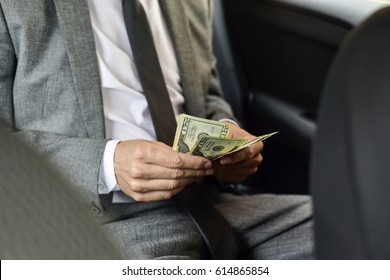 a young caucasian man in an elegant gray suit counts dollar bills sitting in the back seat of a car