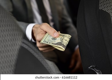 a young caucasian man in an elegant gray suit sitting in the back seat of a car offers a wad of dollar bills to the front