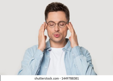 Young caucasian man in eyeglasses massaging temples with close eyes, breathing out, trying to calm down, posing on grey studio background head shot portrait, reducing stress, self-control concept.