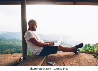 Young caucasian man freelancer working remote on laptop computer while enjoying nature landscape with freedom in mobility.Male traveler connecting to internet on netbook with portable use modem device