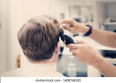 Young caucasian man getting haircut from hairdresser at salon.