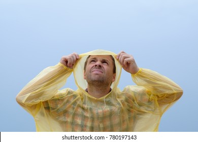 Young caucasian man getting wet under the rain during storm. He stands in yellow raincoat and looking up
