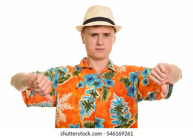 Young Caucasian man giving thumbs down isolated against white background
