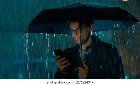 Young Caucasian Man in Glasses, Wearing a Jeans Coat and Square Shirt is Using a Smartphone Under an Umbrella. It's Dark Outside and it is Raining.