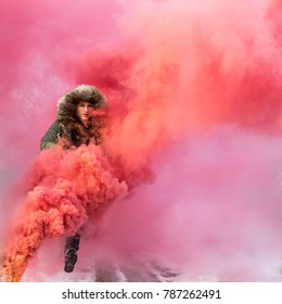 Young caucasian man in a green winter parka jumping over a red smoke bomb on a sombre winter day. Tartu, Estonia.