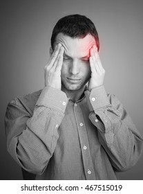 Young Caucasian man with headache. Black and white stylized photo with red local ache spot