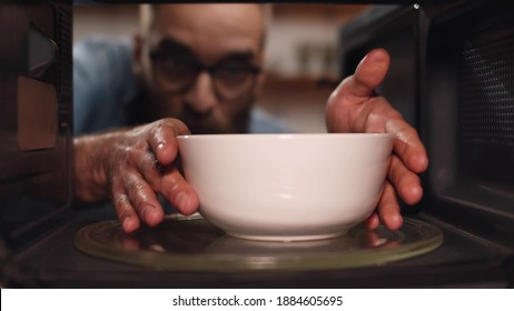 Young caucasian man heating food in microwave oven. View from inside microwave of bearded guy opening door and taking warm bowl with meal for dinner