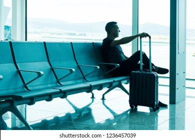 a young caucasian man, with his trolley case, waiting for his flight sitting at the waiting room of an airport