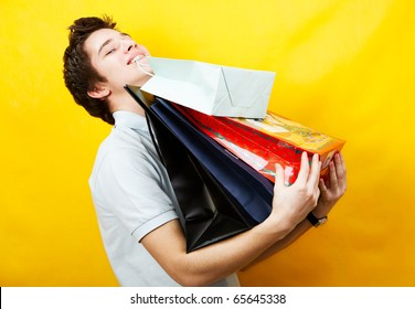 young caucasian man is holding a bunch of shopping bags