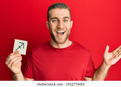 Young caucasian man holding paper with sagittarius zodiac sign celebrating victory with happy smile and winner expression with raised hands