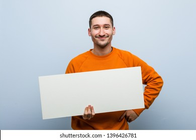 Young caucasian man holding a placard smiling confident with crossed arms.