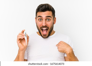 Young caucasian man holding a thermometer isolated Young caucasian man holding  a surprised pointing at himself, smiling broadly.