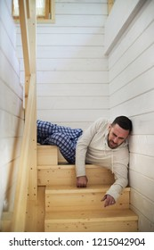 Young Caucasian man in homewear lying on wooden staircase at his house and wincing at pain after falling from high distance