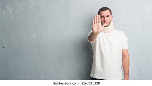 aed9431a8d79 Young caucasian man injured over grey grunge wall wearing neck collar with  open hand doing stop