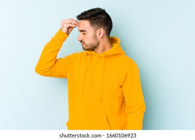 Young caucasian man isolated on blue background having a head ache, touching front of the face.