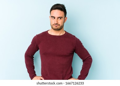 Young caucasian man isolated on blue background confused, feels doubtful and unsure.