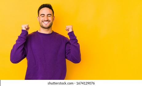 Young caucasian man isolated on yellow bakground celebrating a victory, passion and enthusiasm, happy expression.