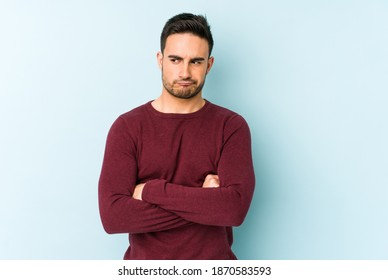 Young caucasian man isolated on blue background frowning face in displeasure, keeps arms folded.