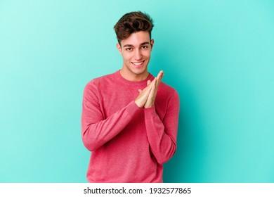 Junge Kaukasier Mann einzeln auf blauem Hintergrund fühlt sich dynamisch und komfortabel, rudernde Hände selbstbewusst.