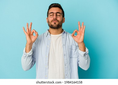 Young caucasian man isolated on blue background relaxes after hard working day, she is performing yoga.