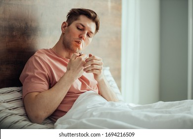 young caucasian man lighting cannabis weed cigarette, going to catch a buzz at home. man leads unhealthy lifestyle, take drugs, marijuana and ganja. smoking treatment, drug treatment