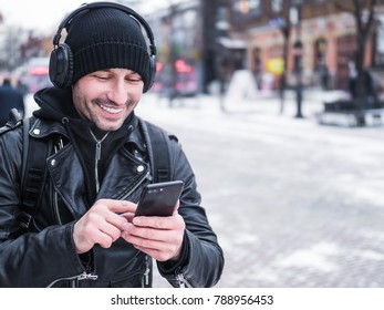 Young Caucasian man listening to music on headphones while walkin by winter town