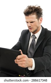 Young Caucasian man looking desperate with laptop indoors over white background.