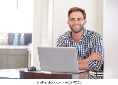 young caucasian man looking into the camera with a big smile while sitting behind his notebook on a bright spring morning with a joyful energy