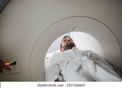 Young Caucasian man  lying on the CT scanner bed.